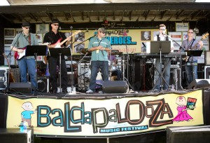 Dustin Simpson (center), of Baldapalooza, stands onstage with Push2Play, one of the bands who played during the fundraiser. Band members are Randy Pinder and Ted Mason on guitar (left), Gentry Myler on drums, Levi Maliwauiki on keyboard, and Jeff Crouch on guitar (right). Photo by Fabiana Huffaker.