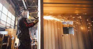 Mike Power uses a grinder to finish cutting the hole for a window in a shipping container at Northwest Building Systems in Boise Tuesday, Dec. 12, 2017. The container will be converted into a portable office and leased out through Design Space Modular Buildings.